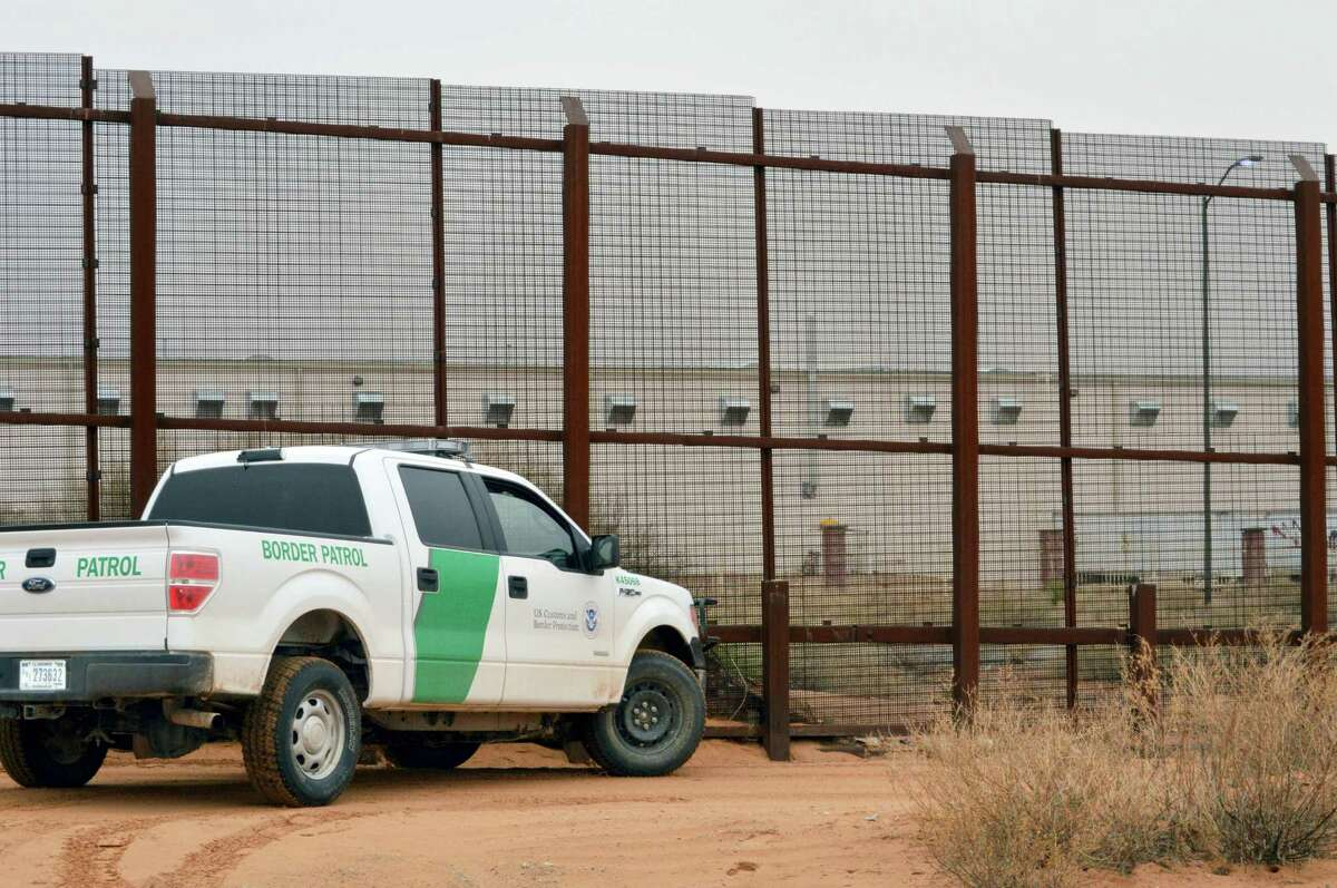 A U.S. Border Patrol vehicle drives next to a U.S.-Mexico border fence in the booming New Mexico town of Santa Teresa. On the Mexican side in San Jeronimo, Mexico, and behind the fence sits a massive Foxconn factory that builds Dell computers for the U.S. market.