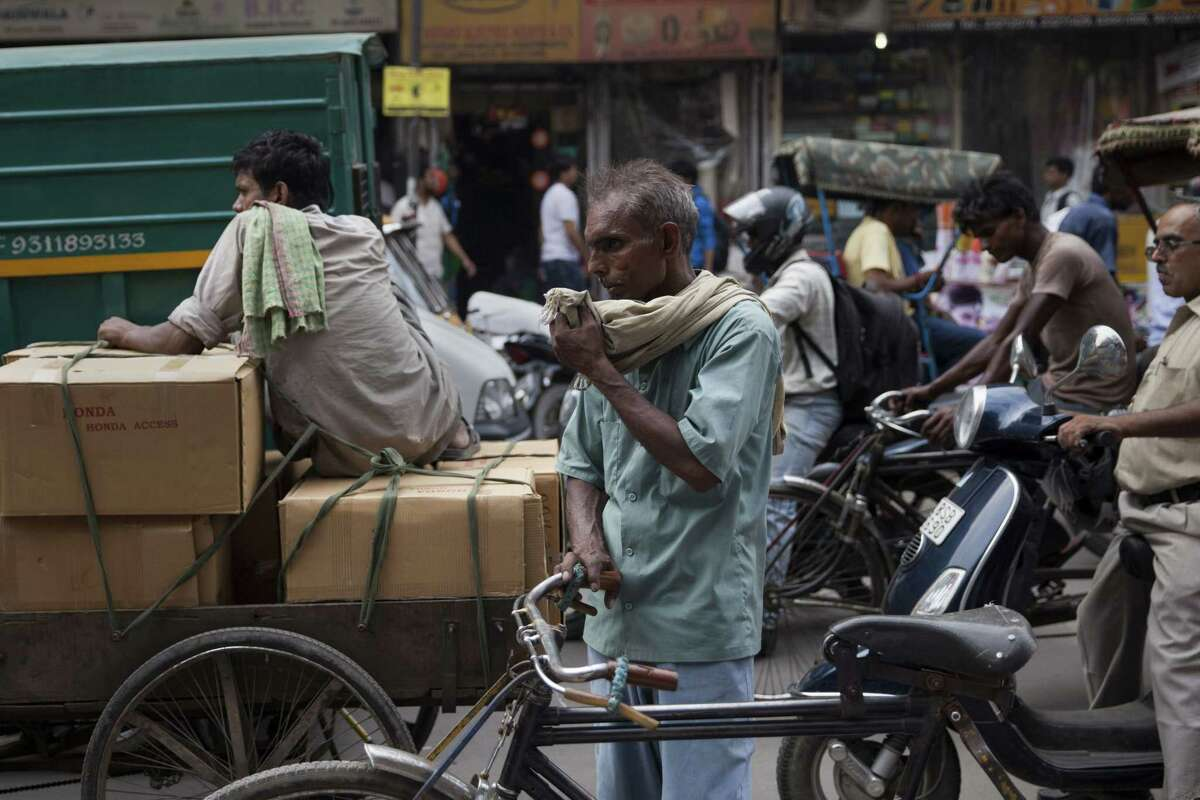 An Indian rickshaw puller pauses as he wipes sweat off his face on a hot summer day in New Delhi, India, Tuesday, June 16, 2015. High humidity prevailed in the national capital after recent showers causing discomfort to people in the city as mercury rose moderately. (AP Photo/Tsering Topgyal)