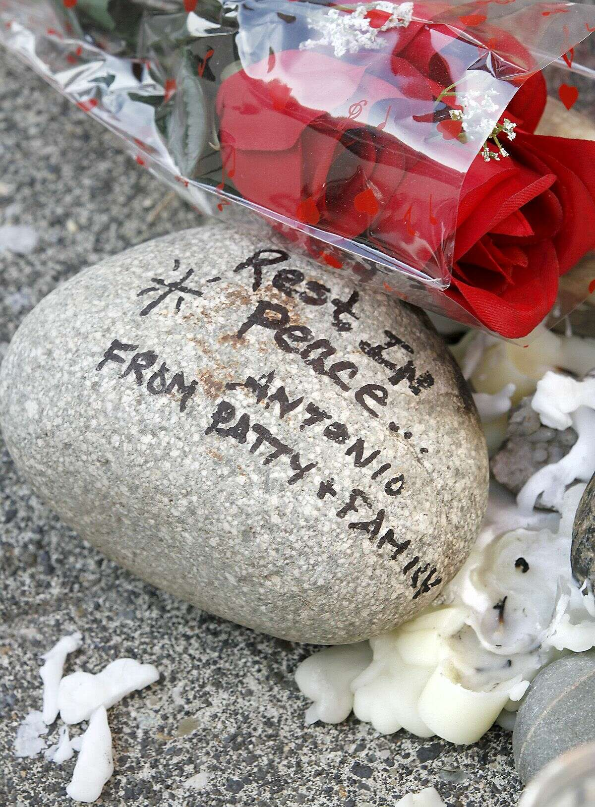 Melted candle wax, a rock and roses are part of an impromptu memorial for Antonio Zambrano-Montes set up on the sidewalk Thursday Feb. 12, 2015 outside of Vinny's Bakery & Cafe in Pasco Wash. It's at the site where the Pasco man was shot and killed by police officers on February 10, 2015. Four people have been shot and killed by police in recent months in this agricultural city of 68,000 in southeastern Washington, and the most recent death of an orchard worker accused of throwing rocks at officers has sparked protests after witnesses said he was running away. (AP Photo/The Tri-City, Herald, Bob Brawdy)