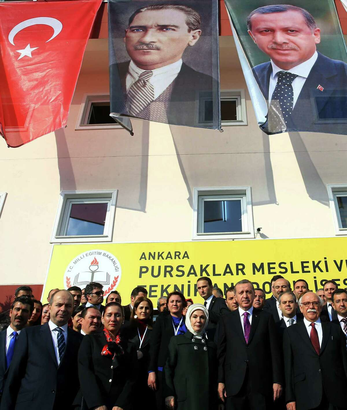 FILE - In this Nov. 18, 2014 file photo, Turkish President Recep Tayyip Erdogan, center-right, and his wife Emine Erdogan pose for photos with officials in the courtyard of a Vocational School for Girls under a poster of Mustafa Kemal Ataturk, center, outside Ankara, Turkey. Turkey has long enshrined the secular ideals of founding father Mustafa Kemal Ataturk, particularly in an education system in which Islamic headscarves were until recently banned in schools and schoolchildren began the day reciting an oath of allegiance to Ataturkís legacy. Now proponents of Turkeyís secular traditions claim President Recep Tayyip Erdogan is overturning those traditions by building a more Islam-focused education system to realize his stated goal of raising ìpious generations.î (AP Photo/File)