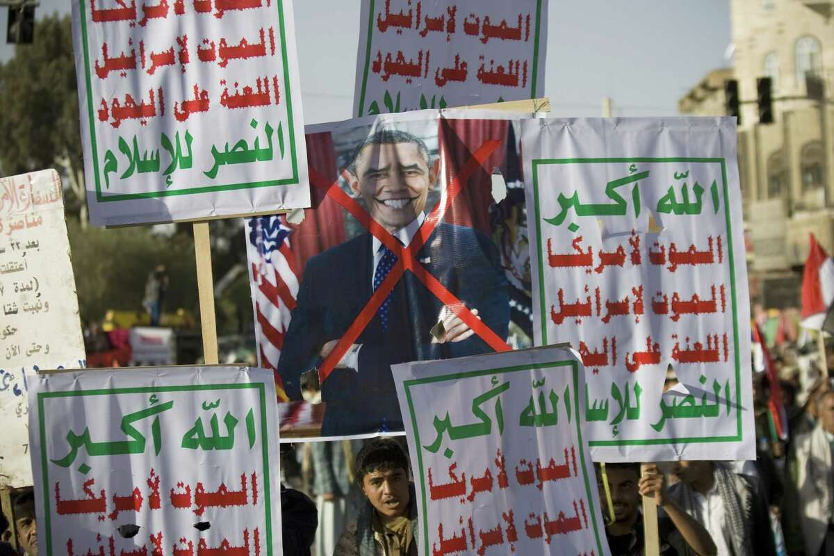 Houthi Shiite Yemenis hold a poster of U.S President Barak Obama and banners in Arabic that read,