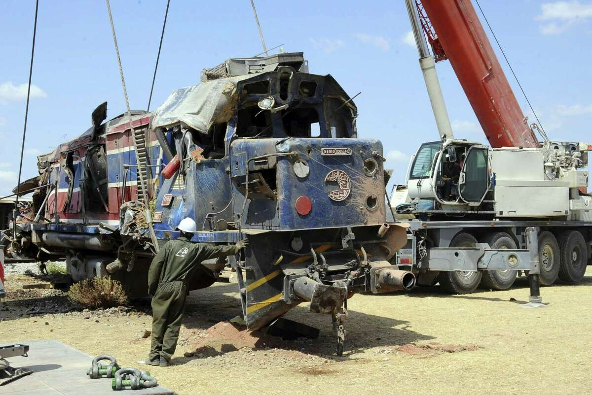 A workers helps removing the wreckage of a train of a train outside Fahs, 60 kilometers (37 miles) from Tunis, Tunisia, Tuesday, June 16, 2015. A Tunisian passenger train smashed into a semi-trailer truck southwest of the capital early Tuesday morning, killing more than a dozen people, according to authorities. (AP Photo/Hassene Dridi)
