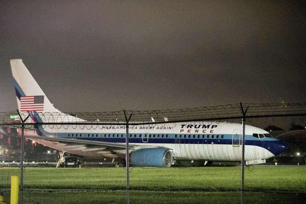 Republican vice presidential candidate Indiana Gov. Mike Pence's campaign airplane sits partially on the tarmac and the grass after sliding off the runway while landing at LaGuardia airport, Thursday, Oct. 27, 2016, in New York.