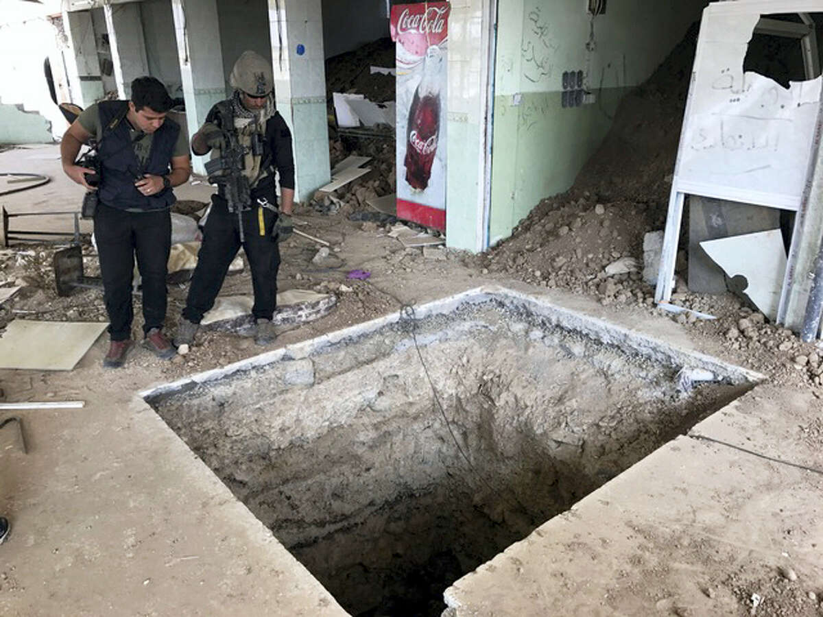 A soldier with Iraq's elite counterterrorism force, left, inspects a tunnel made by Islamic State militants in Bartella, Iraq, Thursday, Oct. 27, 2016. The town of Bartella in northern Iraq lays about 20 kilometres east of Mosul.