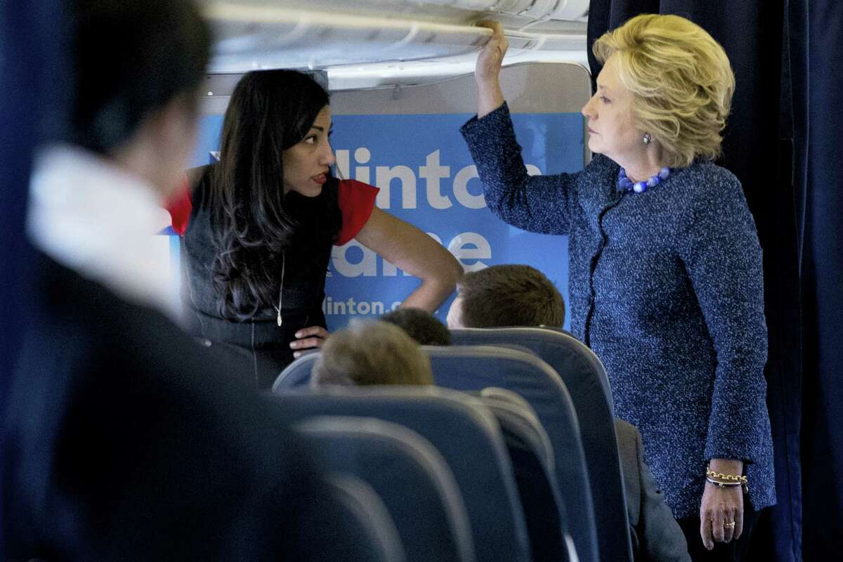 Democratic presidential candidate Hillary Clinton speaks with senior aide Huma Abedin, left, aboard her campaign plane at Westchester County Airport in White Plains, N.Y., Friday, Oct. 28, 2016, before traveling to Iowa for rallies.