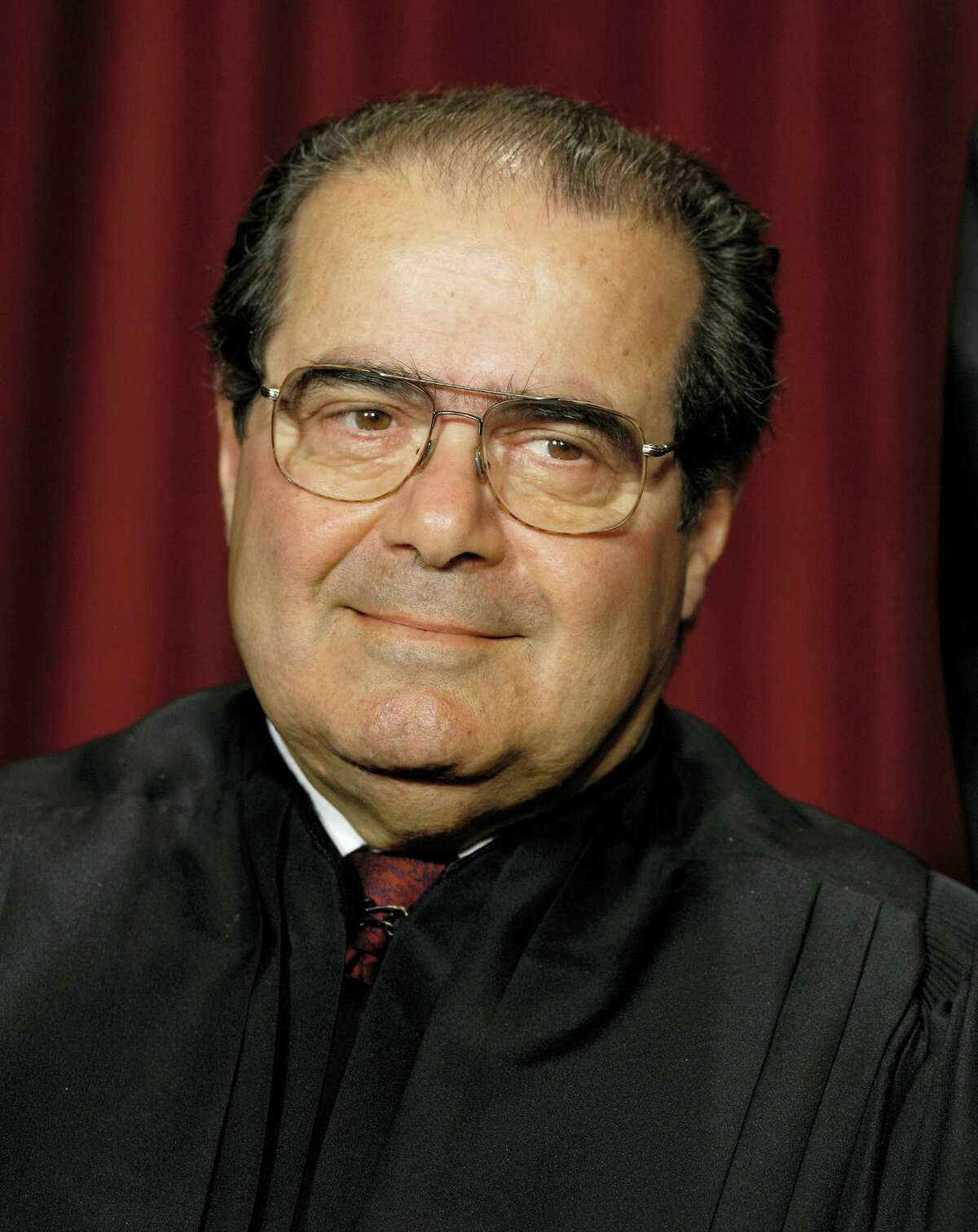 In this Oct. 31, 2005 photo, Associate Justice Antonin Scalia joins the members of the Supreme Court for photos during a group portrait session, at the Supreme Court Building in Washington. On Feb. 13, 2016, the U.S. Marshals Service confirmed that Scalia has died at the age of 79.