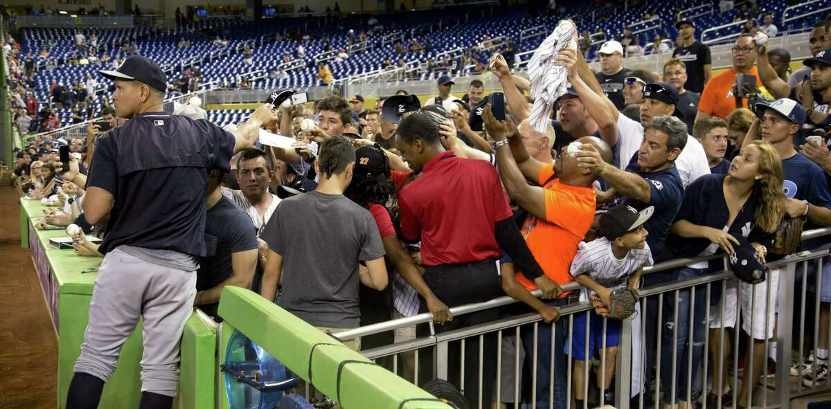 The Yankees' Alex Rodriguez signs autographs for fans before the Monday's game against the Marlins in Miami.
