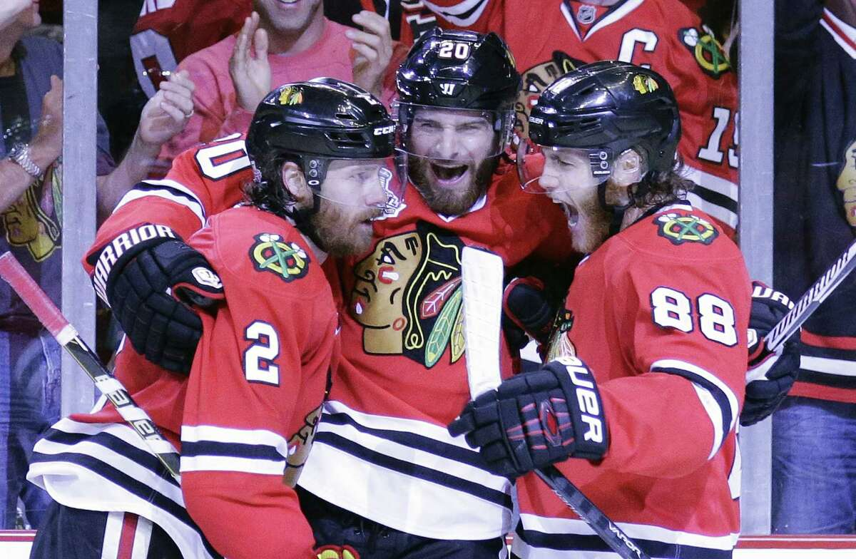 The Blackhawks' Duncan Keith, left, is congratulated by teammates Brandon Saad and Patrick Kane, right, after scoring during the second period on Monday.