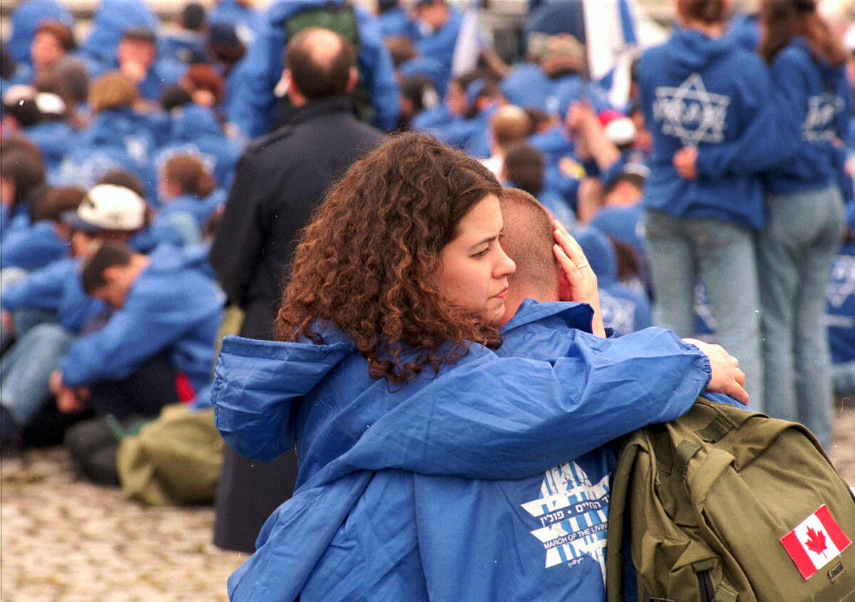 A Canadian pair comfort each other during a ceremony at the fomer Nazi Death Camp Auschwitz-Birkenau during the March of the Living Sunday May 4,1997. About 2,500 Jews from all over the world took part in the March of the Living to commemorate the 6 million victims of the Holocaust.