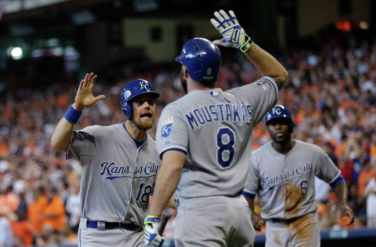The Royals' Ben Zobrist (18) celebrates with teammate Mike Moustakas (8) after he and Lorenzo Cain scored during a five-run rally in the eighth inning on Monday.