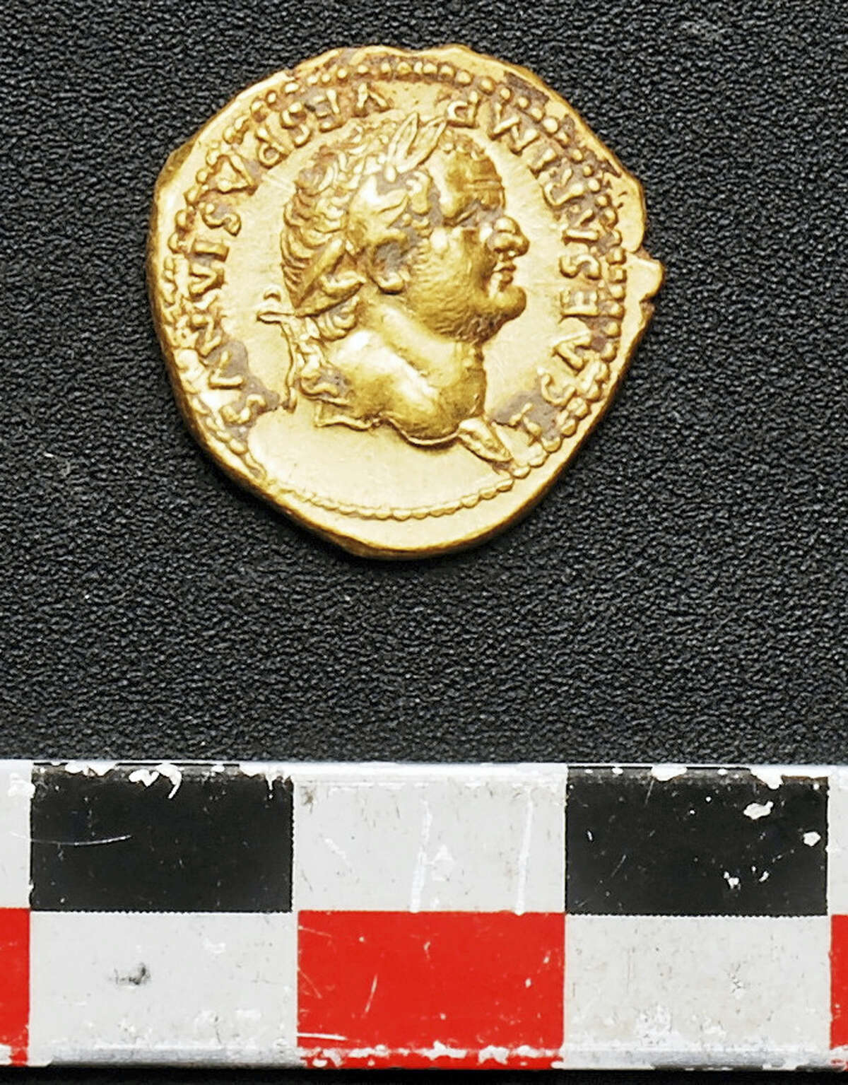 An undated picture made available by the Pompeii Archeological site Press Office, showing a gold coin recently discovered in Pompeii, near Naples, Italy. An Italian and French archaeologist team, digging in the outskirts of Pompeii, have discovered four skeletons and gold coins in the ruins of an ancient shop. Pompeii archaeological site officials said Friday, June 24, 2016, the skeletons are those of young people, including an adolescent girl, who perished in the back of the shop when Mount Vesuvius erupted in 79.