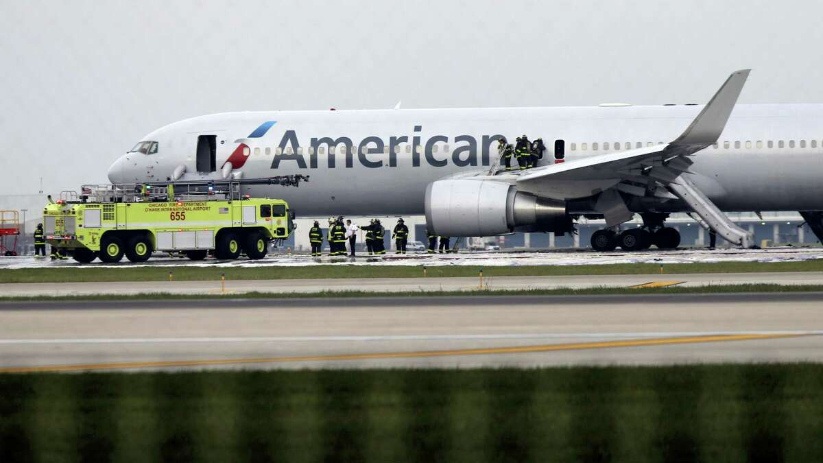 Firefighters extinguish flames from American Airlines Flight 383, flight bound for Miami, which caught fire on the runway at O'Hare International Airport, Friday, Oct. 28, 2016, as it was taking off.
