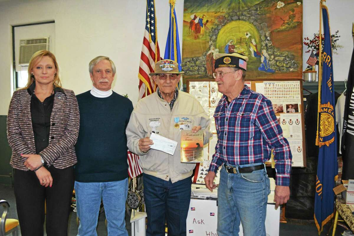 """From left: State Rep. Michelle Cook, Rob Carr, Michael Galitello and Bruce Falls. Galitello presented the Torrington Veteran's Office with the proceeds from his novel, """"Katerina's Tears."""""""