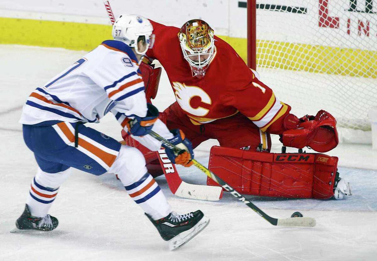 The Oilers' Connor McDavid, left, scores against Flames goalie Brian Elliott during a game earlier this season.