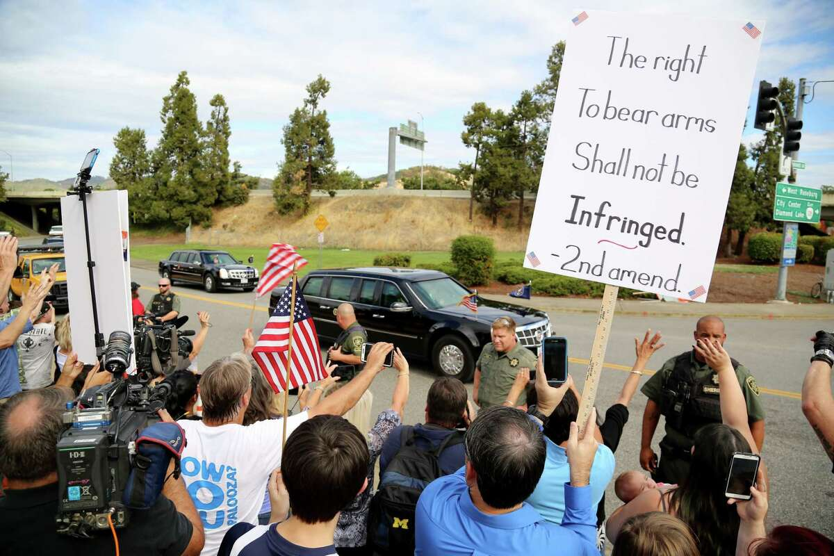 Demonstrators watch as President Barack Obama's motorcade leaves Roseburg High School after a visit with families of victims of the shootings at Umpqua Community College in Roseburg, Ore., Friday. The protesters were angry about Obama's calls for gun restrictions in the wake of the shooting rampage that killed eight students and a teacher at the college.