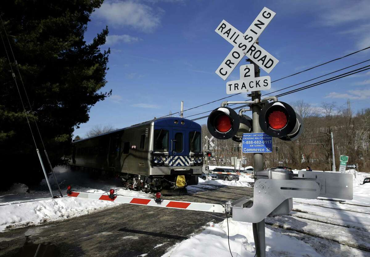 A train passes through the intersection where an SUV was struck by a Metro-North Railroad train in Valhalla, N.Y., Thursday, Feb. 5, 2015. An investigation into what caused a fiery crash that killed a motorist and five rail riders is focusing on how a mother of three described by friends as safety conscious ended up between two crossing gates in her SUV as a commuter train barreled toward her.