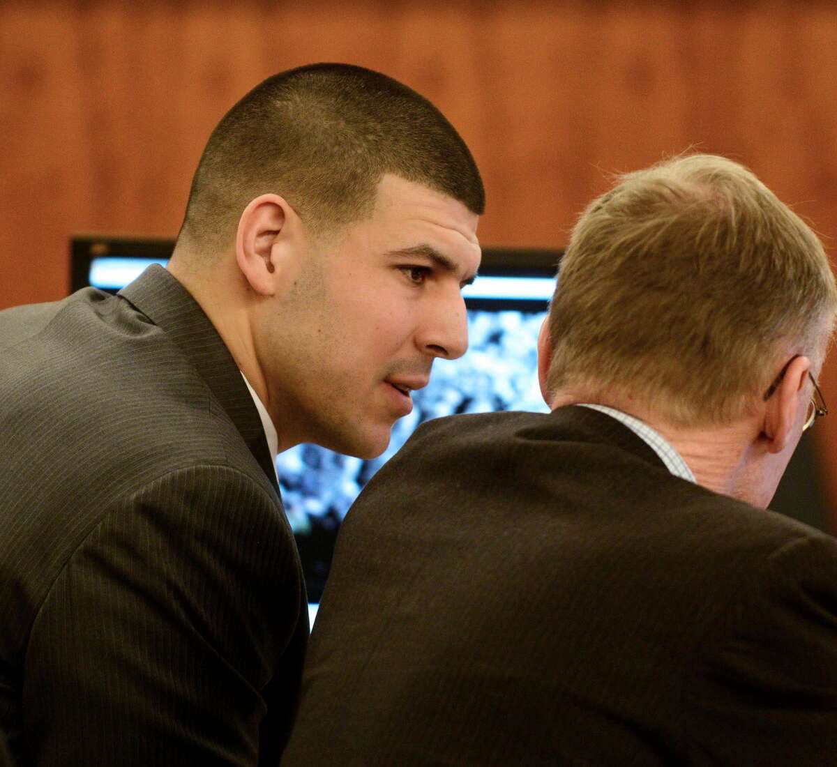 Former New England Patriots tight end Aaron Hernandez, left, talks with his attorney Charles Rankin during his trial at Bristol Superior Court on Wednesday in Fall River, Mass.