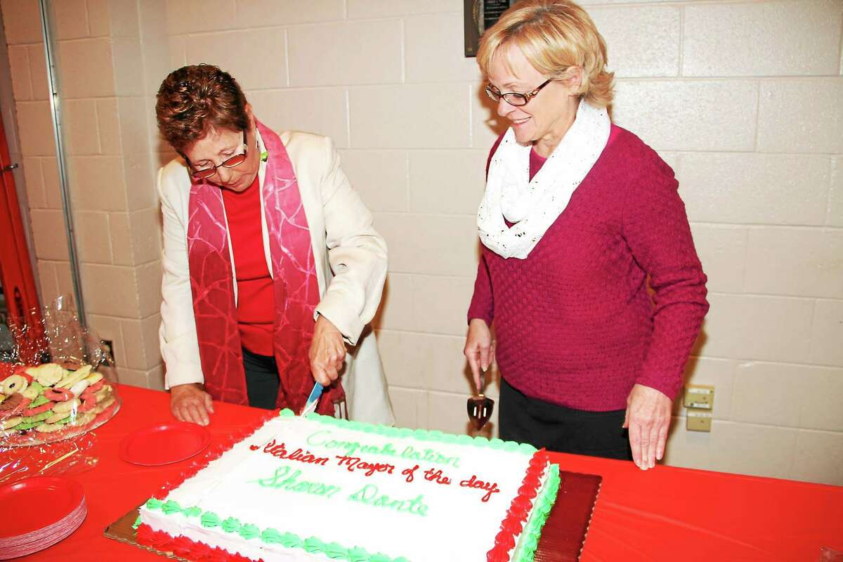 Sharon Dante cuts a celebratory cake with the help of Mayor Elinor C. Carbone after being named Torrington's Italian Mayor of the Day Monday.