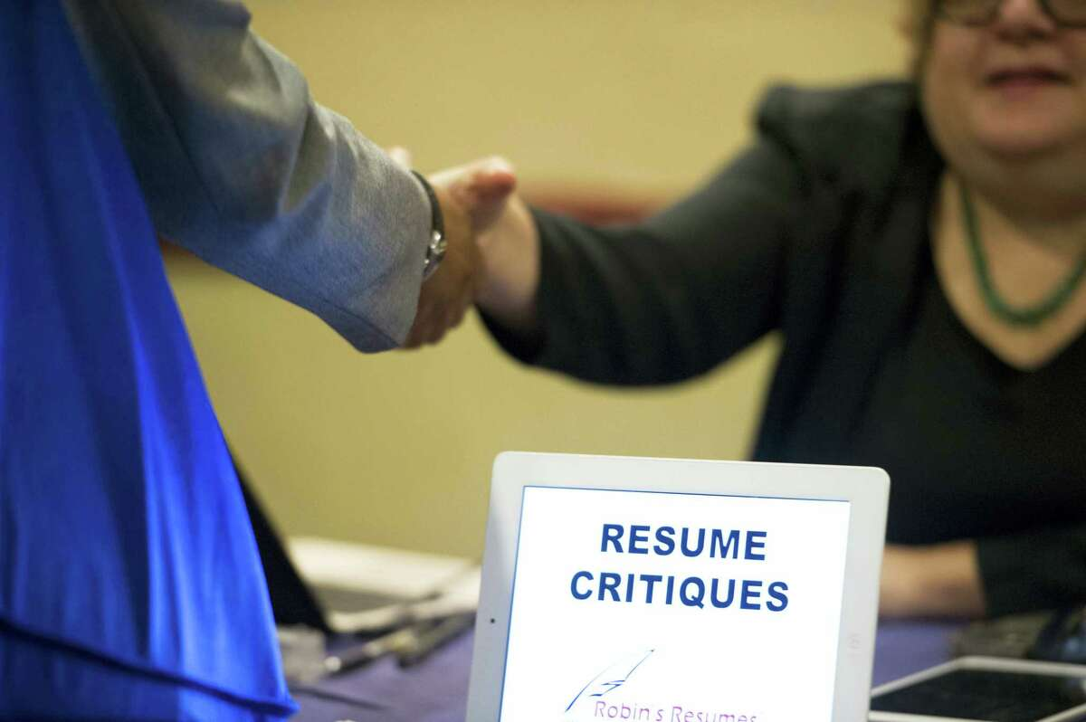 In this Thursday, May 30, 2013, file photo, a job seeker stops at a table offering resume critiques during a job fair held in Atlanta. The Labor Department reported Thursday, Oct. 27, 2016, that fewer Americans sought unemployment aid the week before, a sign that businesses are holding onto their workers and hiring is likely solid.