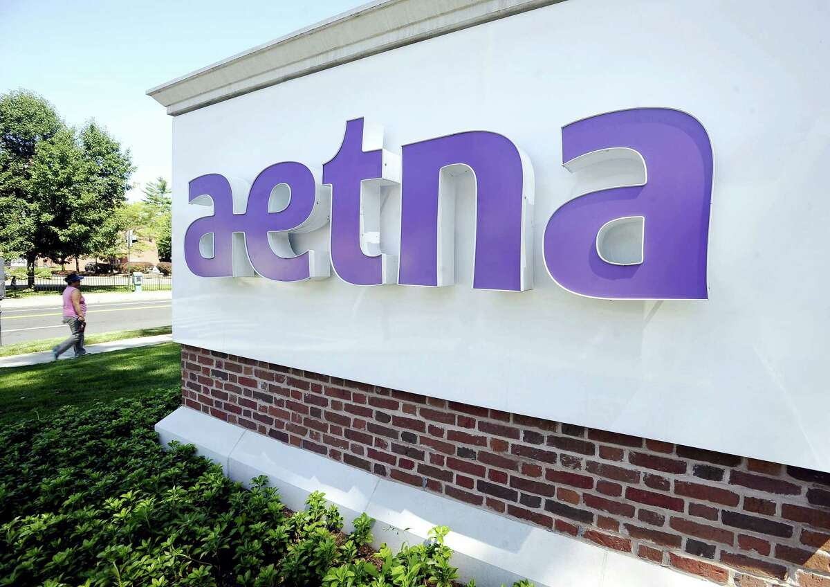 In this Tuesday, Aug. 19, 2014, file photo, a pedestrian walks past a sign for Aetna Inc., at the company headquarters in Hartford, Conn. Aetna reports financial results Thursday, Oct. 27, 2016.