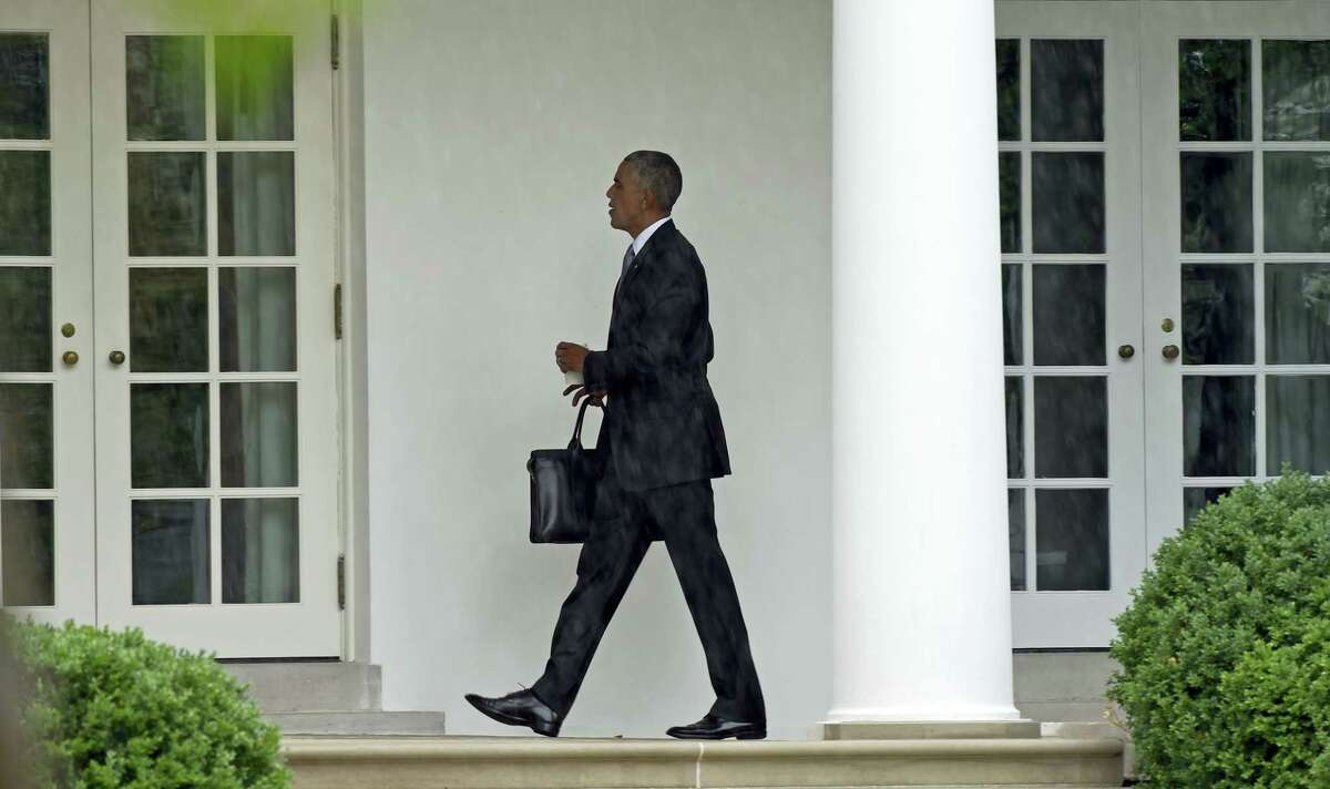 President Barack Obama walks along the Colonnade of the White House in Washington on June 21, 2016, after returning from Walter Reed National Military Medical Center where he visited with injured troops.