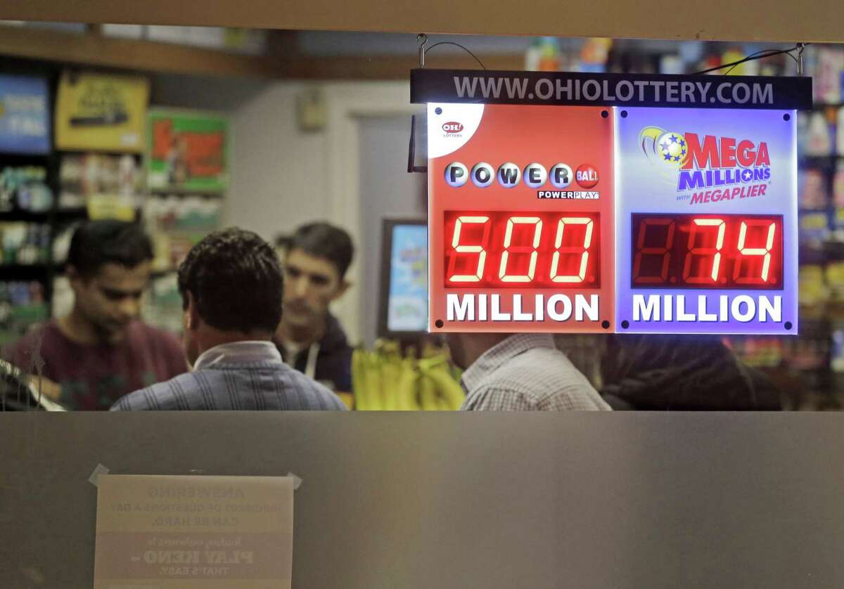 Customers wait to buy lottery tickets at Gateway Newstands in Cleveland Wednesday, Feb. 11, 2015. The Powerball jackpot has climbed to $500 million, making Wednesday night's drawing the fifth largest prize in U.S. history. (AP Photo/Mark Duncan)