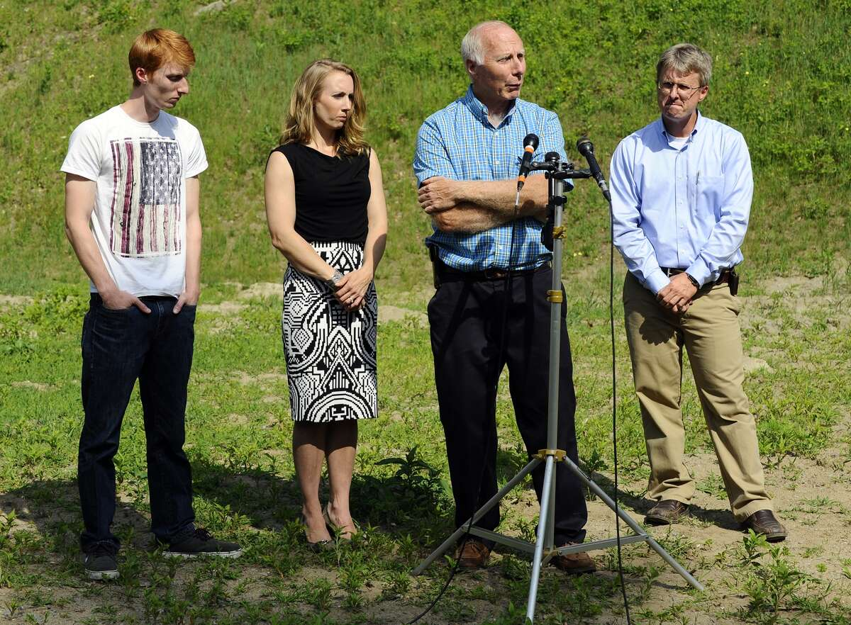 On Thursday, June 11, 2015 in Bolton, Mass., David Broomfield, 25, far left, Corinne Maleski and Andrew Broomfield, 38, stand next to their father, Thomas Broomfield, as he speaks about the recent death of his son, Keith Broomfield, who died while fighting with Kurdish forces against the Islamic State in Syria.