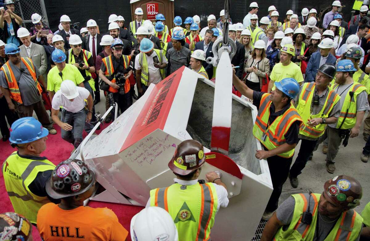 Construction workers gather around to sign a concrete bucket before it is hoisted to the roof of 3 World Trade Center in a topping off ceremony on June 23, 2016 in New York. It's one of three new skyscrapers that replace the twin towers destroyed almost 15 years ago.
