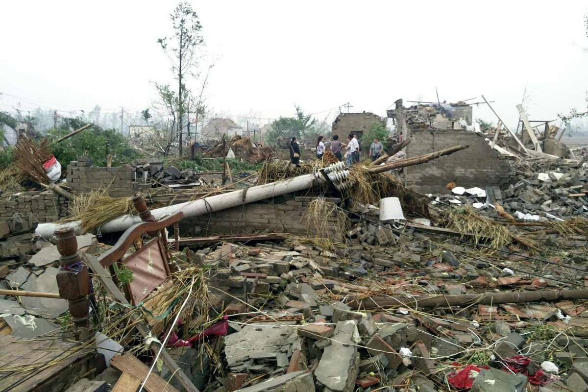 Residents pass houses destroyed in the aftermath of a tornado that hit Funing county, in Yancheng city in eastern China's Jiangsu Province on Thursday, June 23, 2016. A powerful tornado killed dozens and destroyed large numbers of buildings Thursday in the eastern Chinese province of Jiangsu, state media reported.