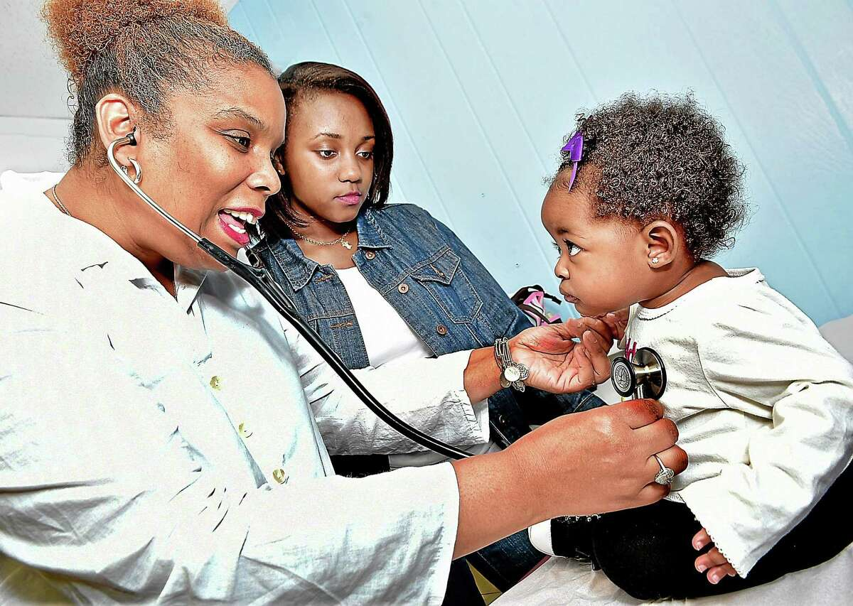 Dr. Tamiko Jackson-McArthur, of New Haven Pediatric & Adolescent Medical Services, Inc. at 1423 Chapel Street in New Haven, examines 7-month-old Maliya Madden. Briana Service, 15, a sophomore, is interning with Dr. Jackson-McArthur twice a week for three months as part of her leadership development class at Hillhouse High School. (Catherine Avalone/New Haven Register)