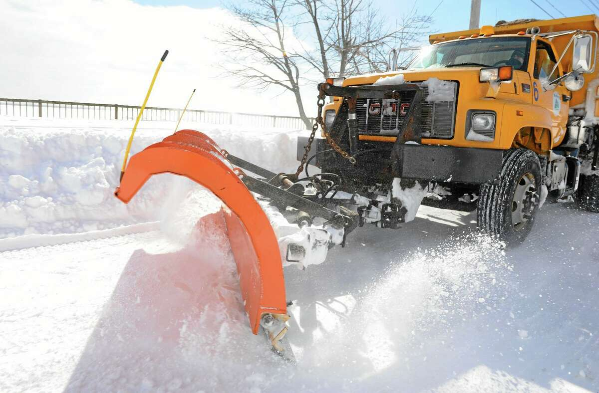 A West Haven city plow speeds by on Beach Street after a blizzard pounded the region in this February 2013 file photo.