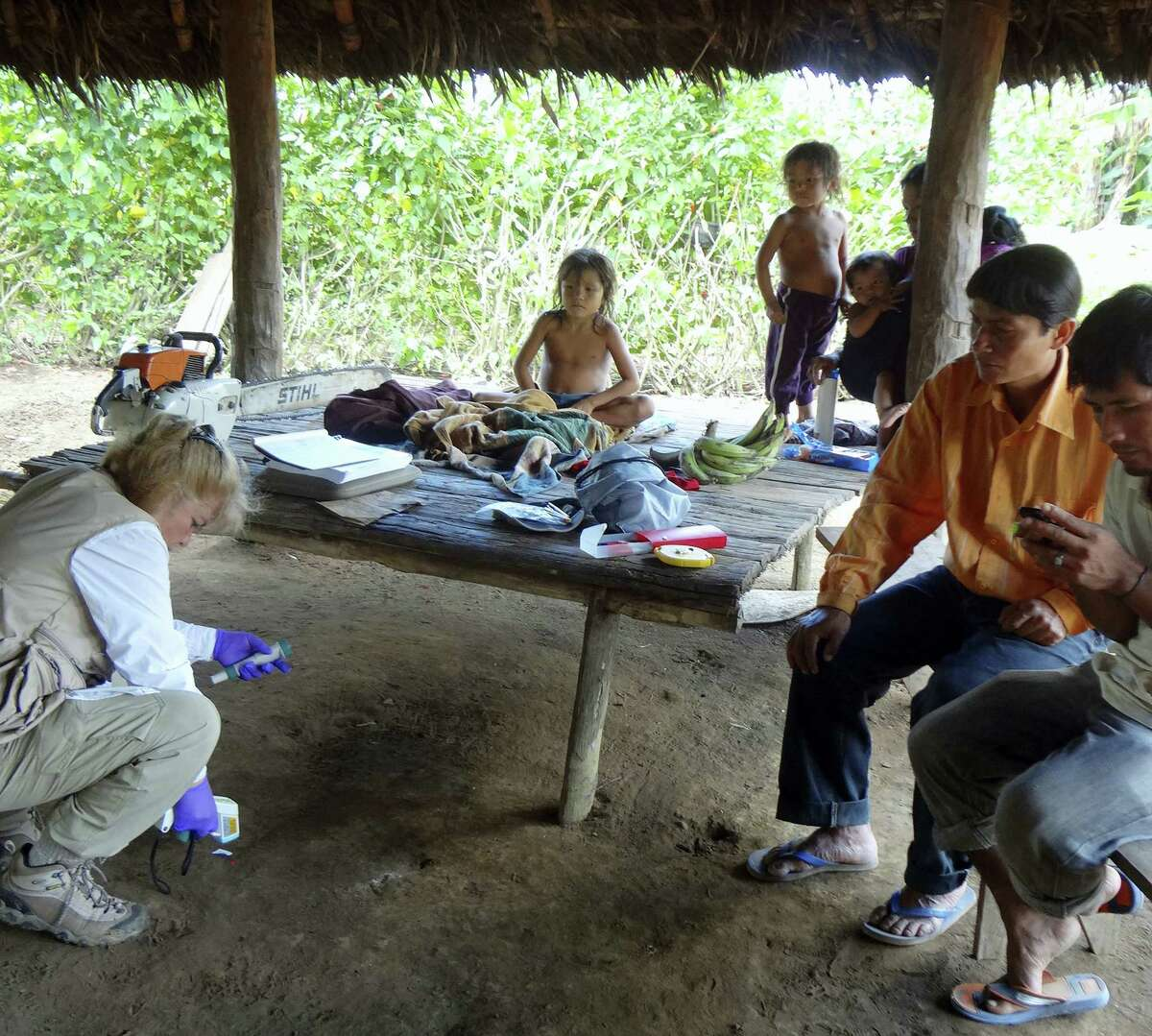 In this photo provided by Science Advances shows microbiologist Maria Gloria Dominguez-Bello, collecting temperature information of the floor at one of the Checherta huts. Whether it's a jungle hut or a high-rise apartment, your home is covered in bacteria, and new research from the Amazon suggests city dwellers might want to open a window.