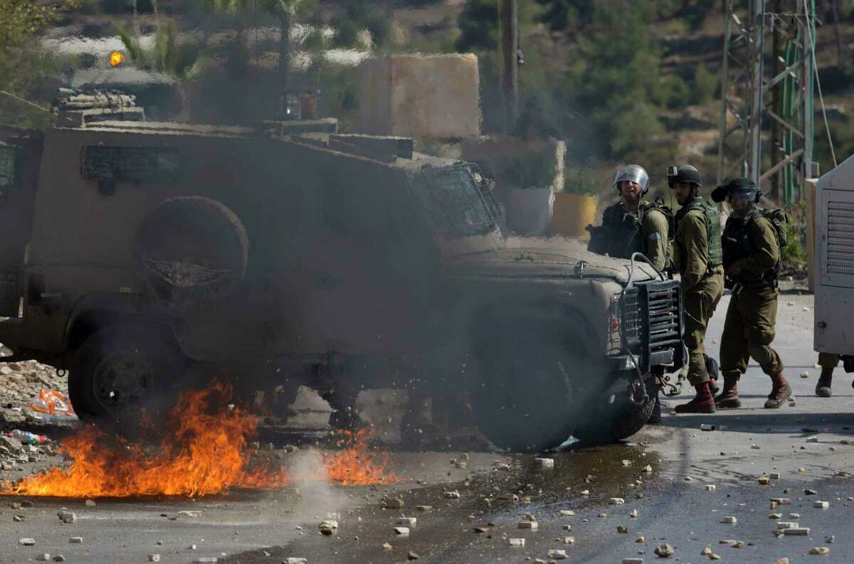 Israeli troops stand behind a vehicle during clashes after the funeral of Ibrahim Awad, 28, in the village of Beit Ummar near the West Bank city of Hebron on Sunday, Oct. 11, 2015.