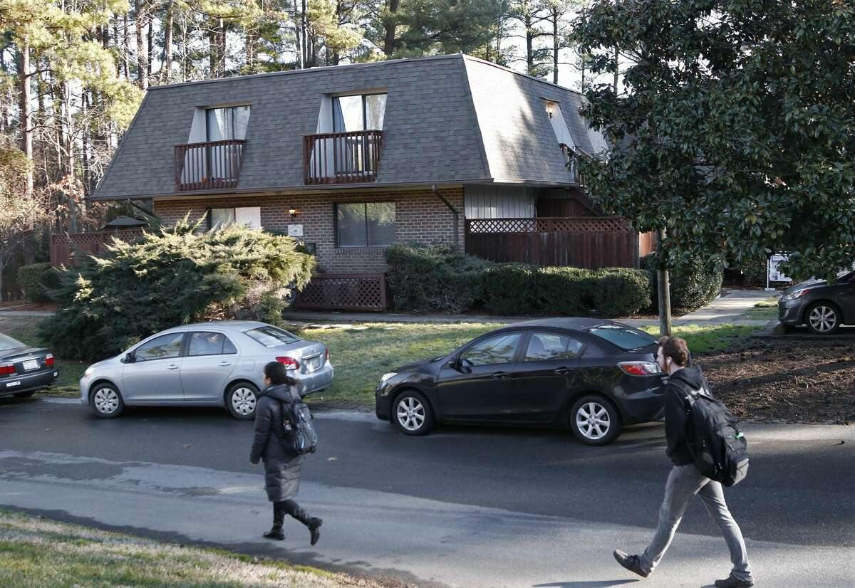 Finley Forest residents walk past the apartment building, Wednesday, Feb. 11, 2015, in Chapel Hill N.C., where three people were killed the day before. A long-running parking dispute between neighbors motivated a man to kill a woman, her newlywed husband and her sister at the quiet condominium complex near the University of North Carolina, police said Wednesday. Craig Stephen Hicks, 46, was charged with three counts of first-degree murder in Tuesday's shooting of Deah Shaddy Barakat, 23, of Chapel Hill; Yusor Mohammad, 21, of Chapel Hill; and Razan Mohammad Abu-Salha, 19, of Raleigh.