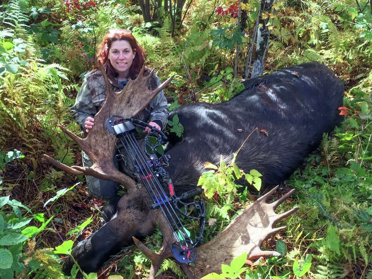 In this Oct. 2, 2015 photo provided by Tammy Miller of Fairfax, Vt., she poses with a moose taken on a hunting trip in Vermont. More women are taking up the largely male dominated sport of hunting as cultural influences, like movie heroines and marketers, make it more socially acceptable and to stock their freezers with local foods.