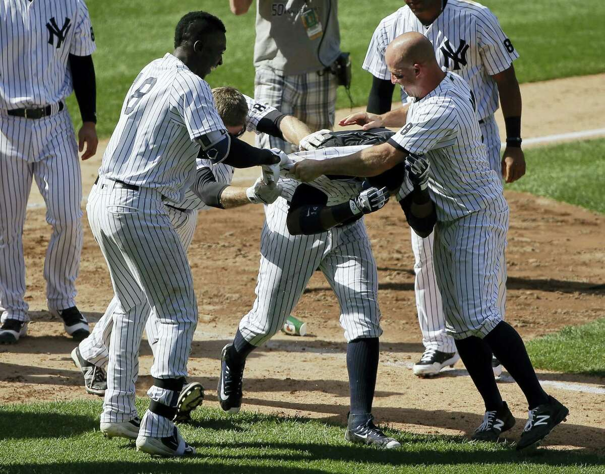 Didi Gregorius (18), Chase Headley, second from left, and Brett Gardner, right, pull off Starlin Castro's jersey after Castro hit a walk-off home run to lead the Yankees to a 9-8 win over the Colorado Rockies Wednesday.