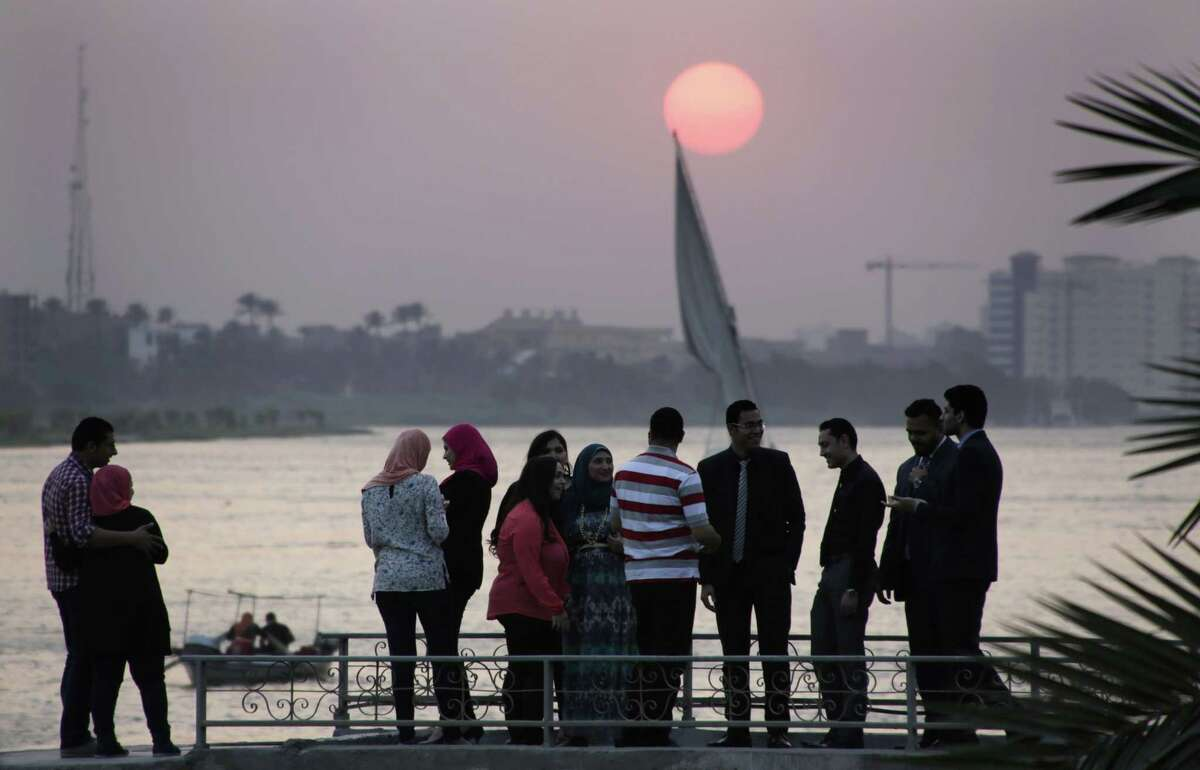 Egyptians pose for pictures as others have a small talk at sunset on the Nile River in Cairo, Egypt, Wednesday, June 3, 2015. (AP Photo/Amr Nabil)