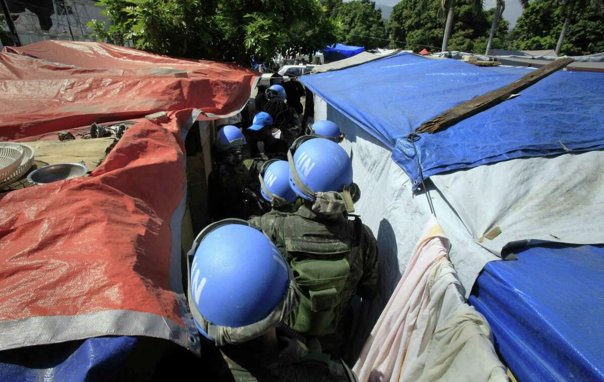 FILE - In this Tuesday, March 30, 2010 file photo, United Nations peacekeepers patrol an earthquake survivors makeshift camp in Port-au-Prince. In 2015, troubled by peacekeepers' sexual relationships with the people they are meant to protect, the UN has quietly started helping with DNA collection to prove paternity claims for so-called