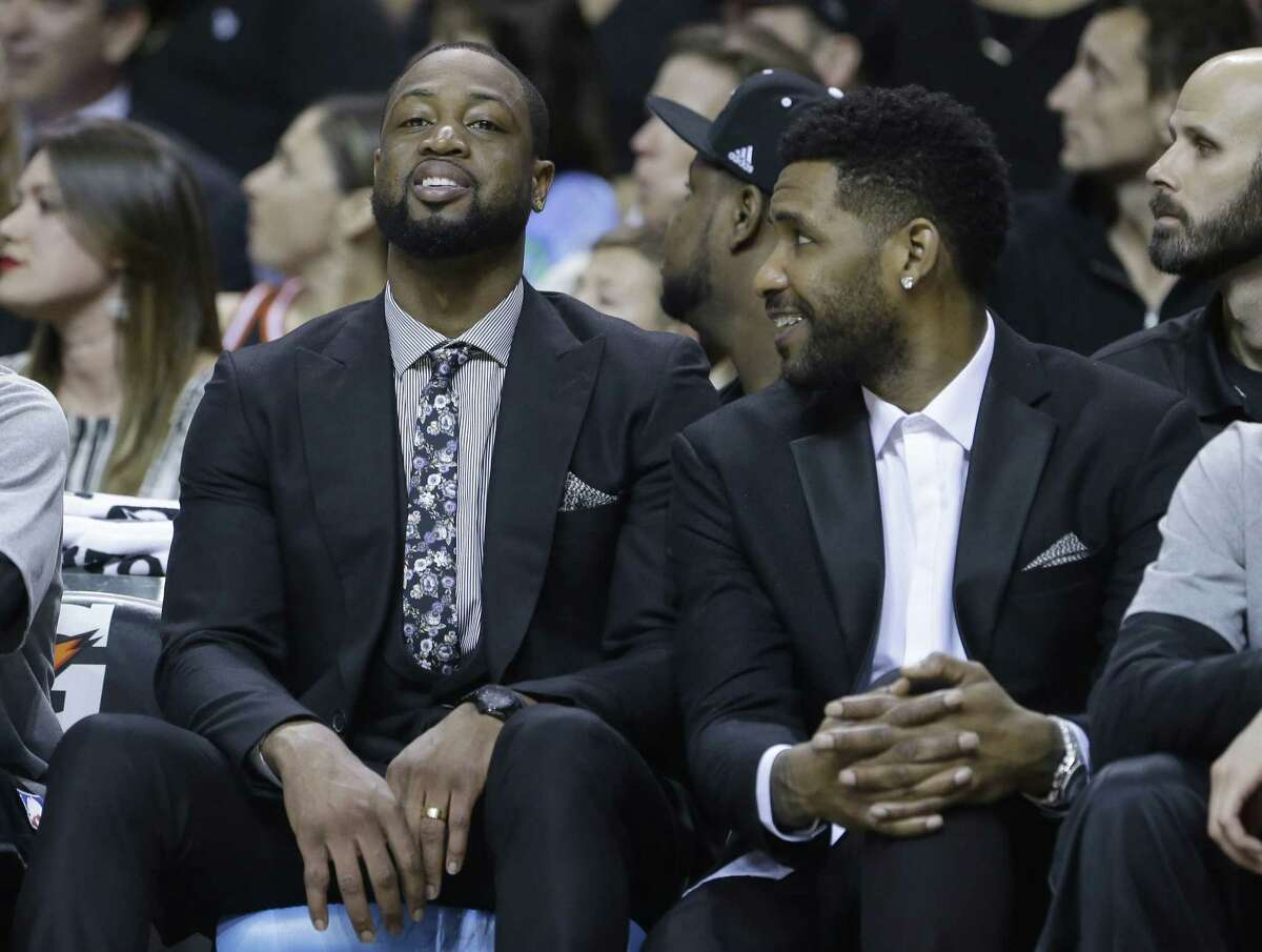 Heat guard Dwyane Wade, left, and forward Shawne Williams sit on the bench during Monday's game against the New York Knicks in Miami.