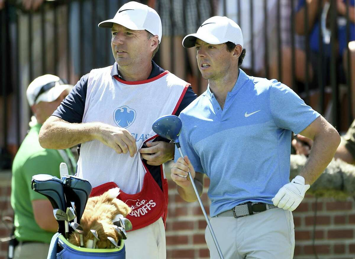 In this Aug. 28, 2016 photo, Rory McIlroy of Northern Ireland, right, and his caddy, J. P. Fitzgerald look down the fairway before McIlroy tees off from the first hole during the final round of The Barclays golf tournament in Farmingdale, N.Y.