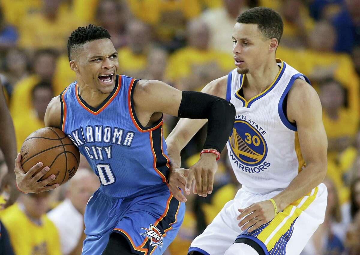 In this May 18, 2016 photo, Oklahoma City Thunder guard Russell Westbrook (0) reacts as he is guarded by Golden State Warriors guard Stephen Curry (30) during the second half of Game 2 of the NBA basketball Western Conference finals in Oakland, Calif.