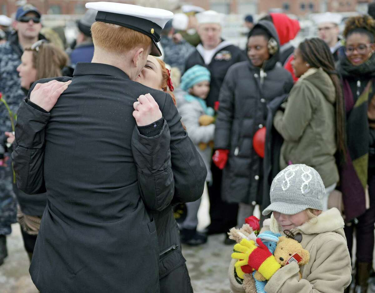 U.S. Navy Chief Petty Officer Chris Jacobson kisses his fiancé Carmen Armstrong as her daughter Evie Armstrong, 8, holds the stuffed animal gifts she received from Jacobson when the navy attack submarine USS Missouri (SSN 780) returned to the Navy Submarine Bast in Groton, Conn., Friday, Feb. 12, 2016 following a six-month deployment to the European Command area of responsibility. The Missouri, the seventh sub in the Virginia-class, made port calls in Faslane, Scotland, Rota, Spain and Brest, France during the deployment.