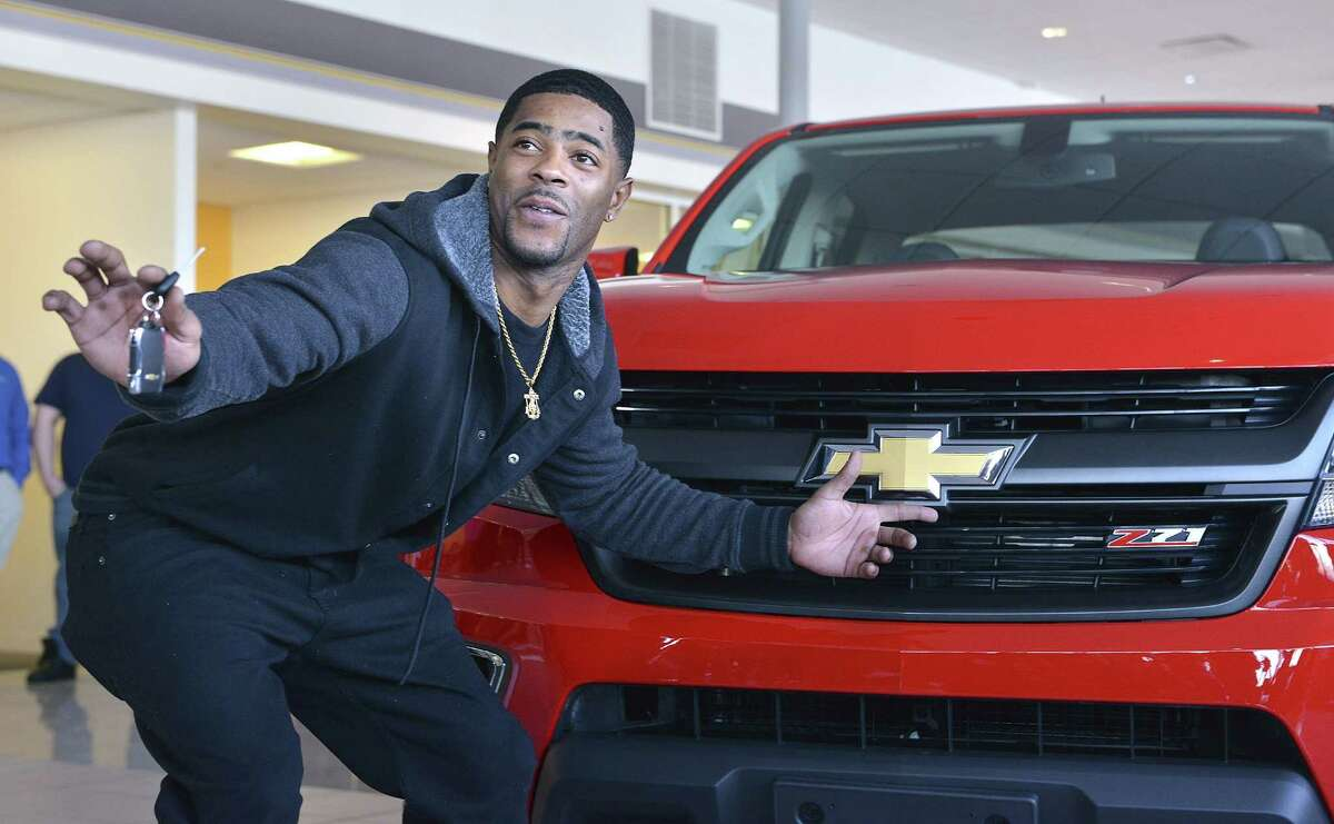 New England Patriots cornerback Malcolm Butler poses with his new Chevrolet pickup truck Tuesday at a dealership in Norwood, Mass.
