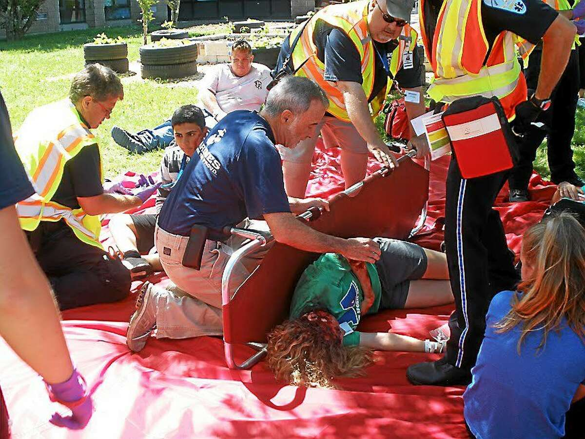 Volunteers playing victims await medical treatment at triage areas set up as part of a disaster triage training drill for area hospitals and first responders at East School in Torrington on Saturday.