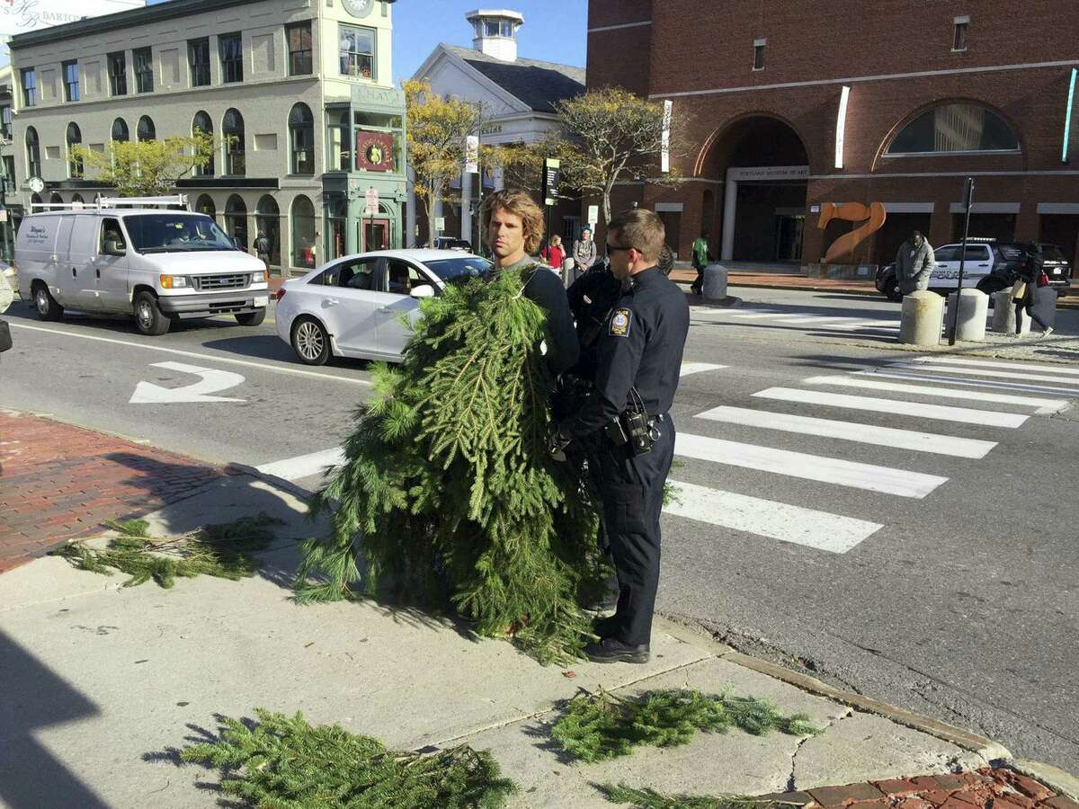 In this Monday, Oct. 24, 2016, photo Asher Woodworth, center left, is dressed as a tree while standing with law enforcement officials near an intersection in Portland, Maine. Woodworth, who was arrested for blocking traffic while dressed as an evergreen tree, says the public display was intended to be performance art. He was released on $60 bail.