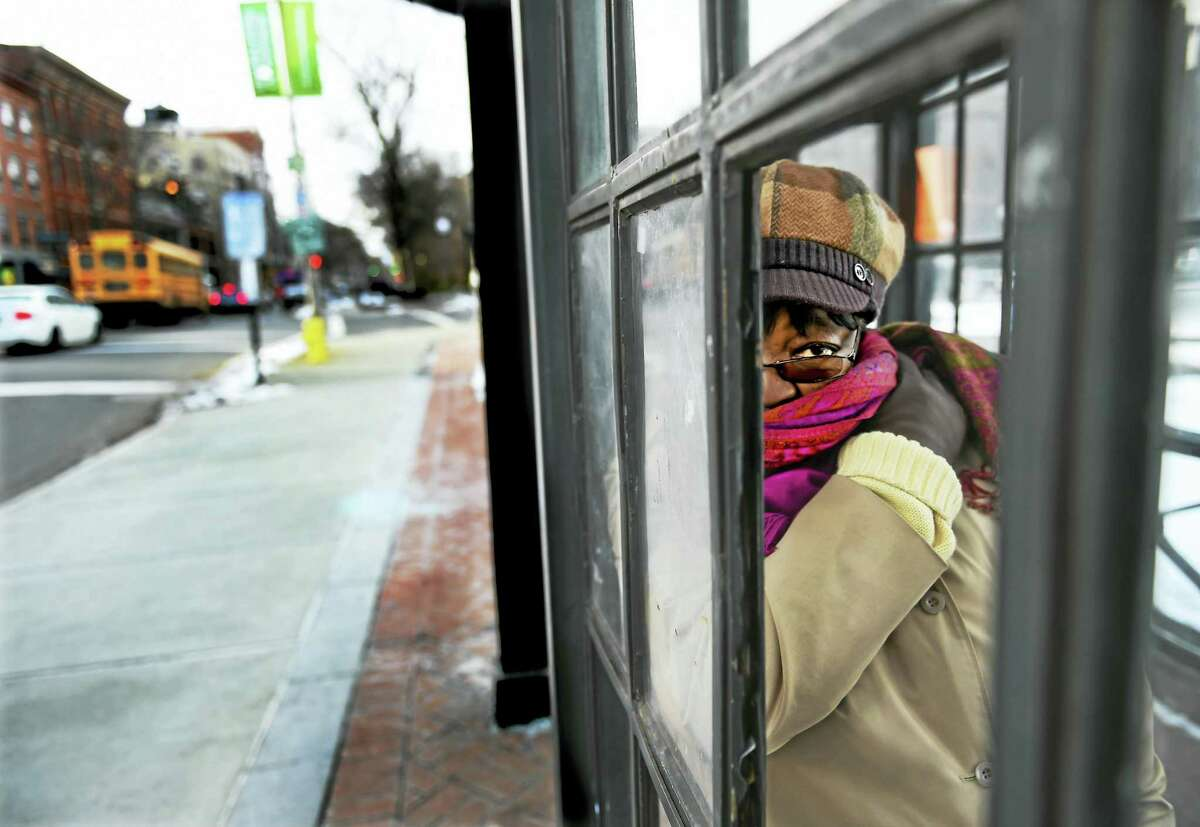 Gladys Brown of New Haven huddles in an enclosed bus stop Thursday afternoon on Chapel Street in New Haven as she waits for her bus to arrive.