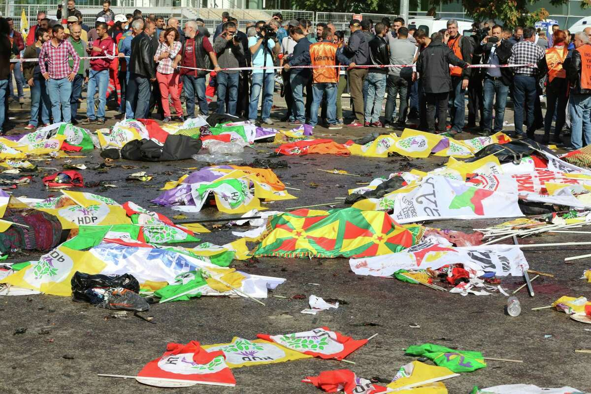 Bodies of victims are covered with flags and banners at the site of an explosion in Ankara, Turkey, Saturday, Oct. 10, 2015. Turkey's health minister says two bomb explosions in the Turkish capital have killed scores of people. The explosions occurred minutes apart near Ankara's main train station as people were gathering for a rally, organized by the country's public sector workers' trade union and other civic society groups. The rally aimed to call for an end to the renewed violence between Kurdish rebels and Turkish security forces.