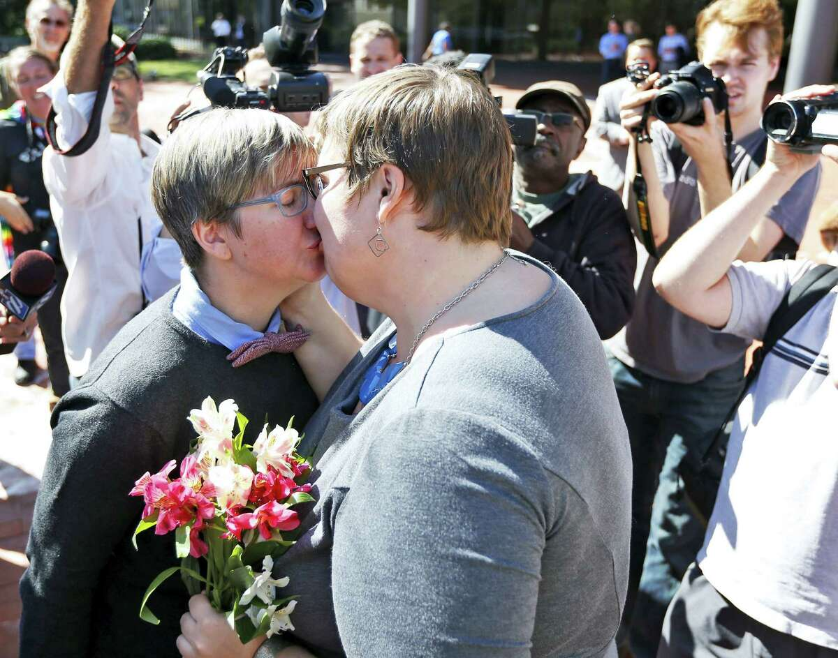 Nicole Pries, left, and Lindsey Oliver share a kiss as they celebrate being one of the first same-sex couples in Virginia to be married, Monday, Oct. 6, 2014, outside a Richmond Court building in Richmond, Va.