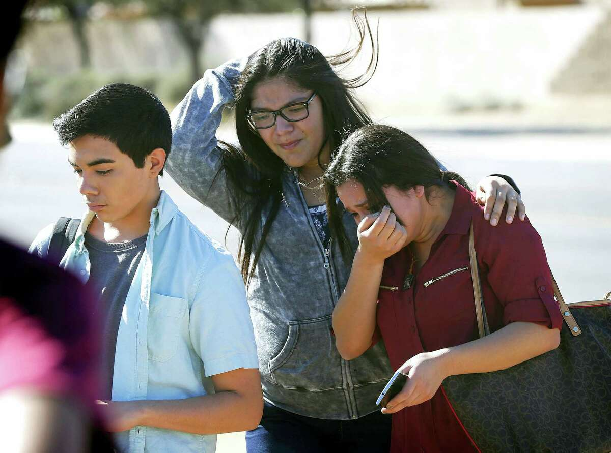 Students walk to their parents after being released from lockdown, Friday, Feb. 12, 2016, in Glendale, Ariz., after two students were shot and killed at Independence High School in the Phoenix suburb.