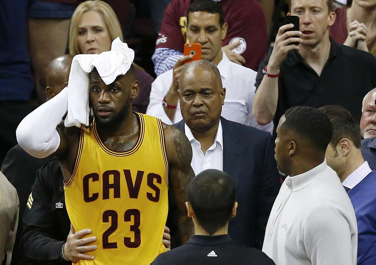 Cleveland Cavaliers forward LeBron James (23) holds a towel to his head after he collided with a TV cameraman during the first half of Game 4 on Thursday.